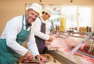 Fleischer beim /ubereiten von Fleisch