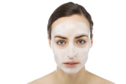 Eine junge Frau mit Gesichstmaske zur Hautpflege