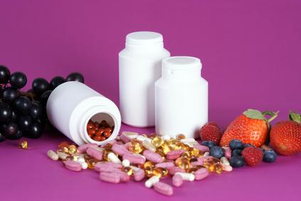 Ein haufen Pillen daneben einige Früchte