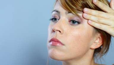 Eine Frau untersucht ihre Haut nach Unreinheiten