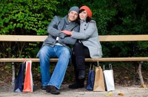 Ein Pärchen auf einer Bank im Park mit Winterklamotten