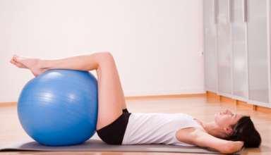 junge frau mit gymnastikball trainiert